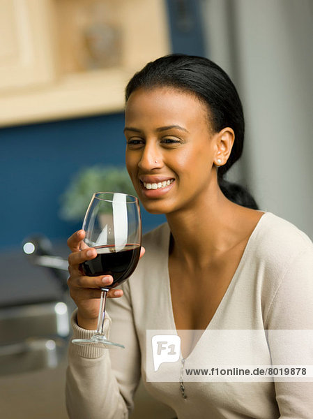 Young woman holding glass of red wine and smiling