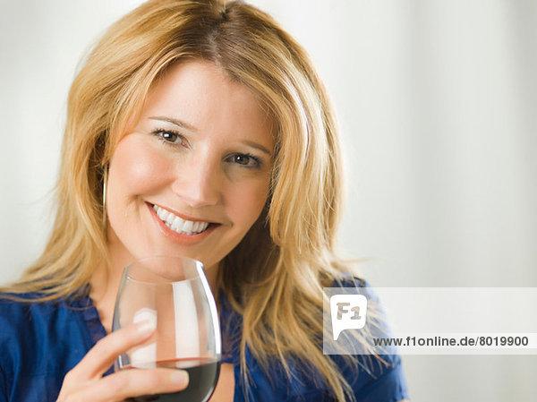 Mittlere erwachsene Frau mit einem Glas Wein  Portrait