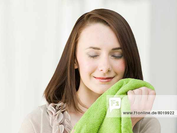 Young woman holding green towel with eyes closed