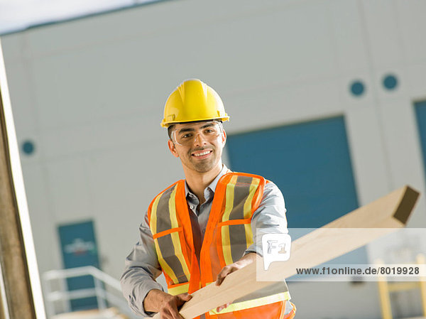 Mid adult construction worker holding wood