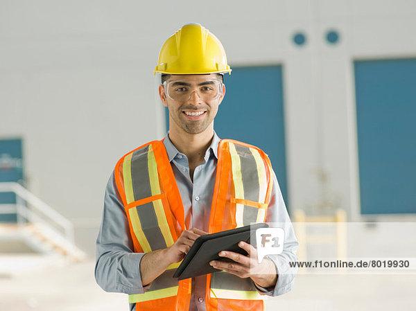 Mid adult construction worker using digital tablet  portrait