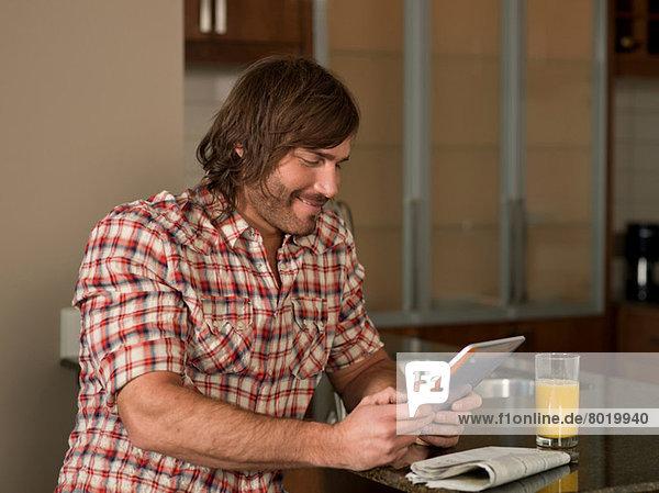 Mid adult man using digital tablet in kitchen