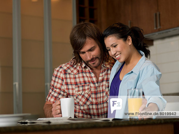 Junge Frau und mittelgroßer Mann beim Zeitungslesen in der Küche
