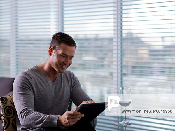Mid adult man sitting and using digital tablet