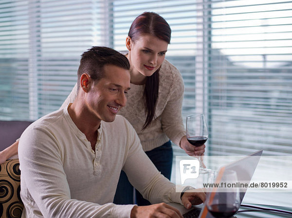 Young woman and mid adult man enjoyng wine and using laptop