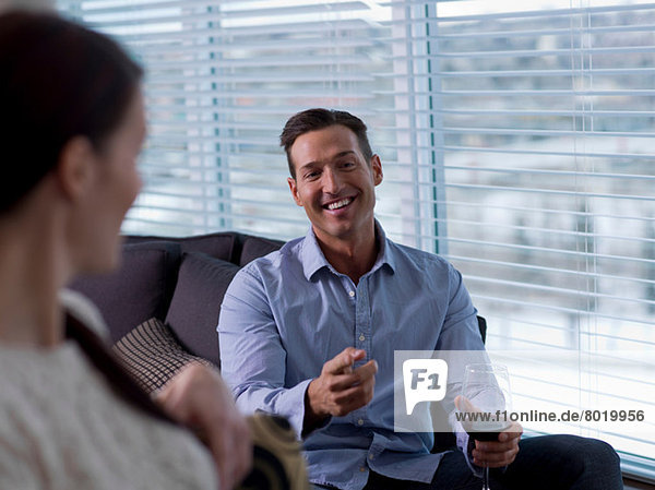 Mid adult man relaxing with young woman and glass of wine