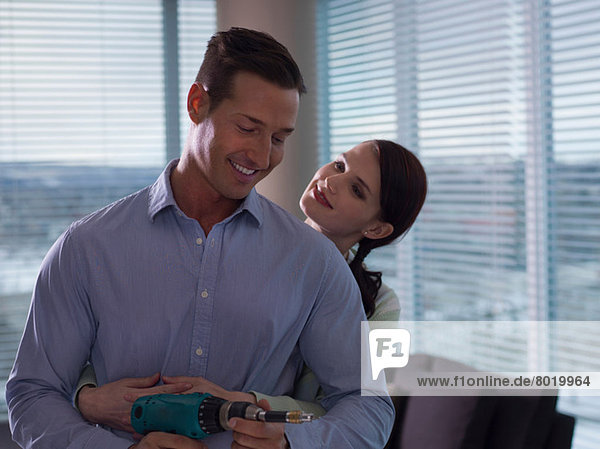 Young woman embracing mid adult man holding hand drill
