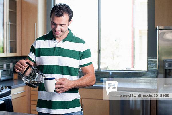 Junger Mann gießt Kaffee aus der Kanne in die Küche  lächelnd