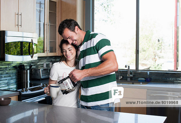 Young couple pouring coffee from pot in kitchen  smiling