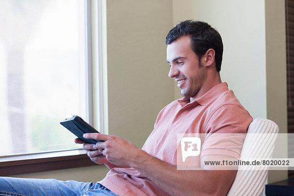 Junger Mann mit elektronischem Buch  lächelnd