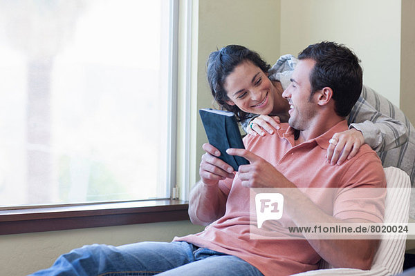 Young couple using electronic book  smiling