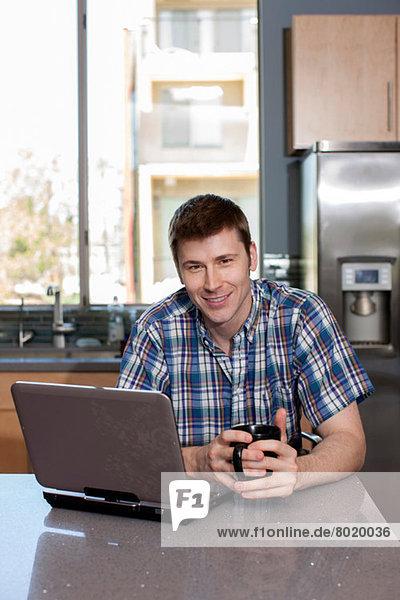 Mittlerer Erwachsener Mann mit Laptop in der Küche  Porträt