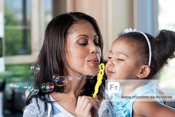 Mittlere erwachsene Mutter und junges Mädchen beim Blasenblasen  Nahaufnahme