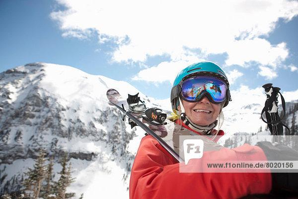 Junge Frau in Skibekleidung hält Skier über die Schulter  lächelnd