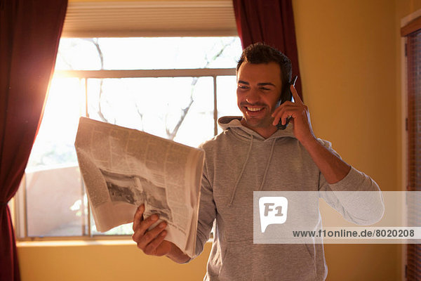 Young man looking at newspaper and using mobile phone in hotel room  smiling
