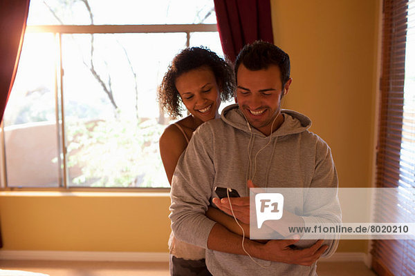 Young couple listening to mp3 player in hotel room  smiling