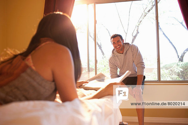 Young woman lying on bed with man sitting on window sill of hotel room