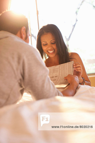 Young couple on bed reading newspaper