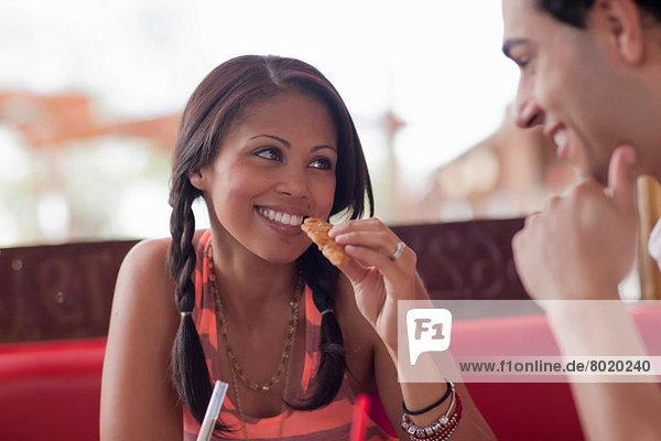 Junge Frau beim Essen mit Freund im Diner  lächelnd