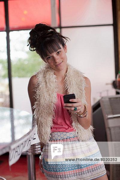 Junge Frau mit Handy im Diner  Portrait