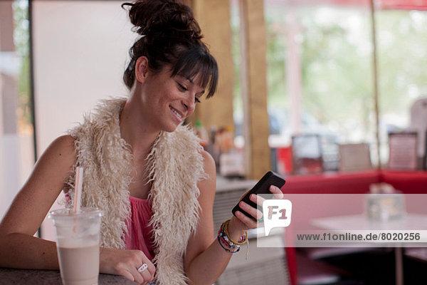 Junge Frau beim Anblick des Handys im Diner