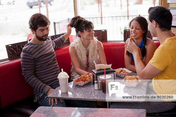 Vier Freunde sitzen zusammen im Diner  lächelnd
