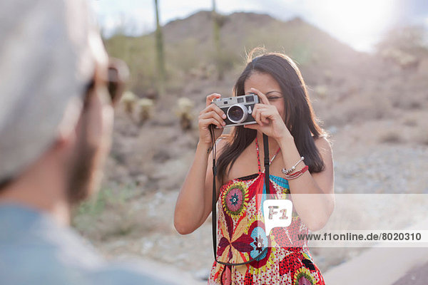Young woman photographing boyfriend on desert road