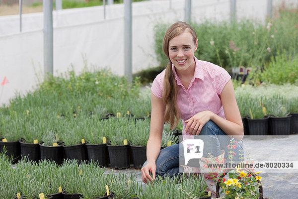 Mittlere erwachsene Frau kauernd bei Pflanzen im Gartencenter  Portrait
