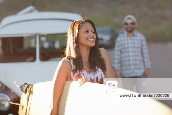 Junge Frau mit Surfbrett auf Roadtrip  lächelnd