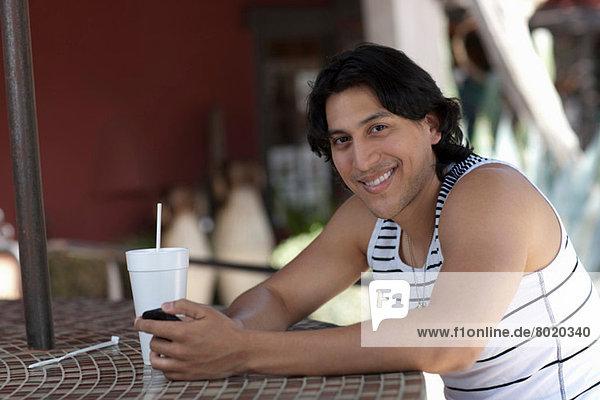 Junger Mann mit Handy im Außencafé  Portrait