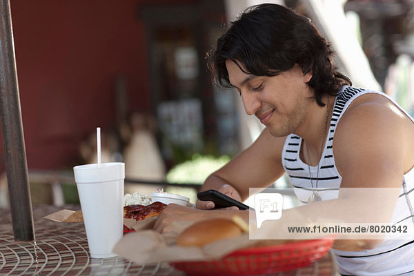 Junger Mann schaut auf Handy im Outdoor-Café  lächelnd