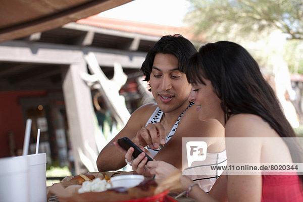 Junges Paar  das im Outdoor-Café auf sein Handy schaut  lächelnd