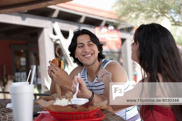 Junges Paar beim Essen im Café im Freien  lächelnd