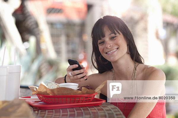 Junge Frau mit Handy im Außencafé  Portrait