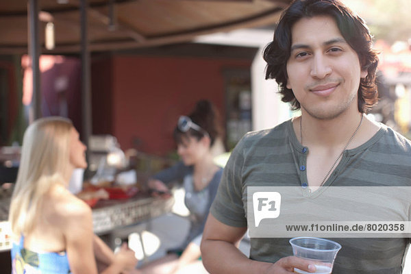 Young man holding drink and smiling in outdoor cafe  portrait
