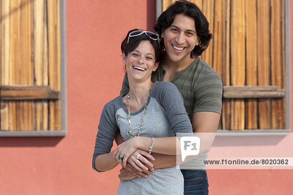 Junges Paar umarmend und lächelnd,  Portrait