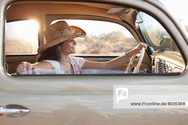 Junge Frau im Auto sitzend  lächelnd