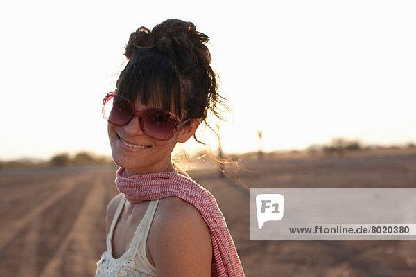 Junge Frau mit Sonnenbrille in der Wüste  Portrait