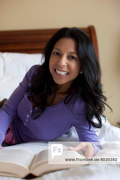 Reife Frau auf dem Bett liegend mit Buch  Porträt