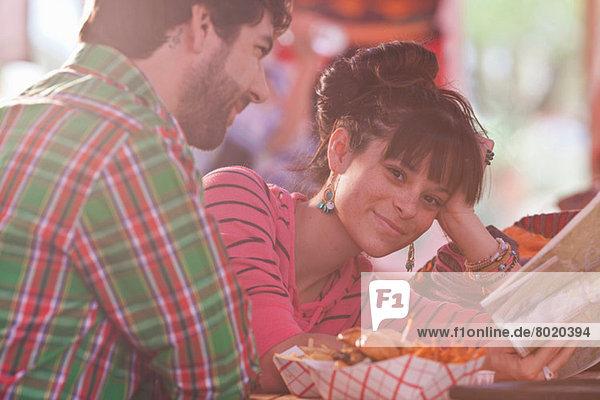 Junge Frau hält Karte mit Mann im sonnendurchfluteten Restaurant