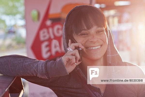 Junge Frau mit Handy im sonnendurchfluteten Diner  lächelnd