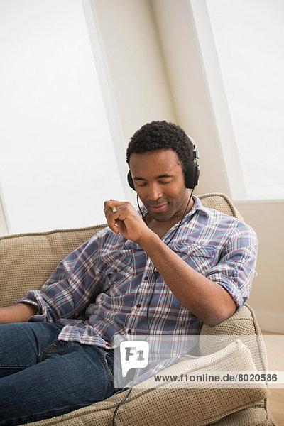Mann mit Kopfhörer beim Musikhören auf dem Sofa