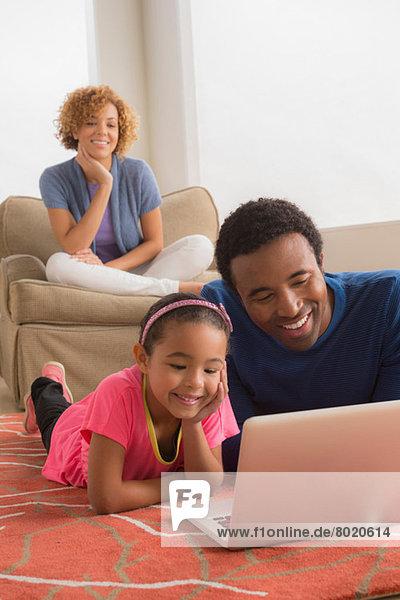 Vater und Tochter auf dem Boden mit Laptop