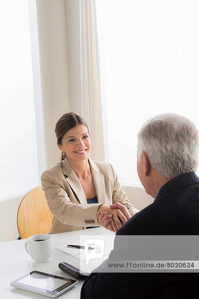 Mann und Frau schütteln sich die Hände beim Treffen