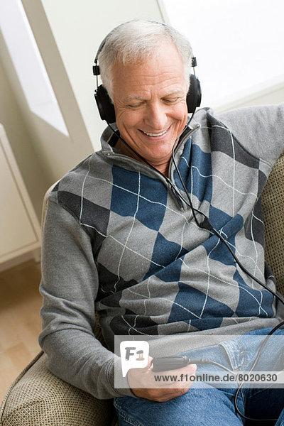 Senior Mann mit Kopfhörer und Musik hören