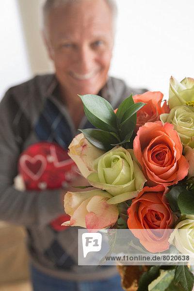Älterer Mann mit einem Strauß Blumen und Schokolade