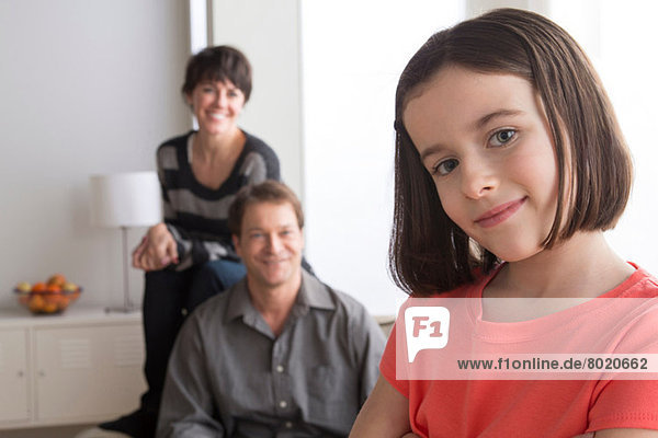 Porträt eines Mädchens mit Eltern im Hintergrund