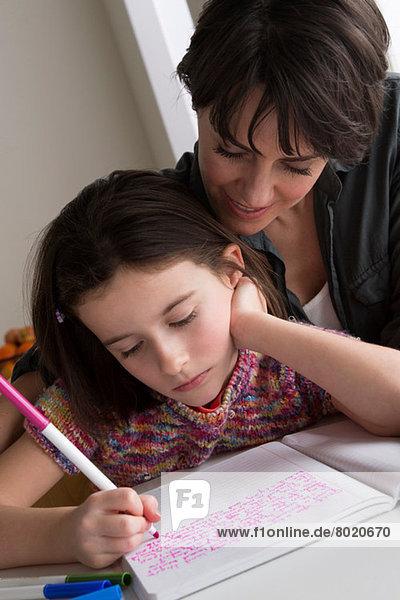 Mutter beobachtet Tochter beim Schreiben