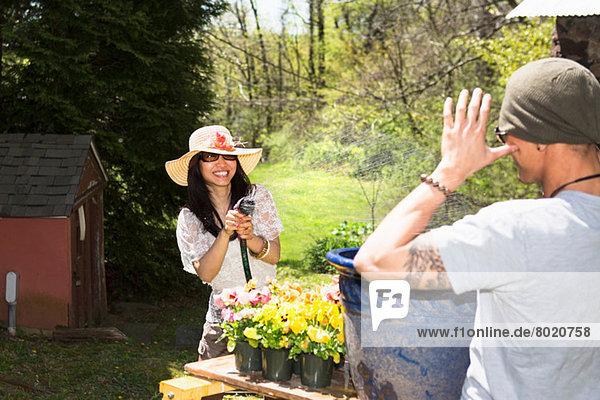 Frau spritzt Mann mit Schlauch