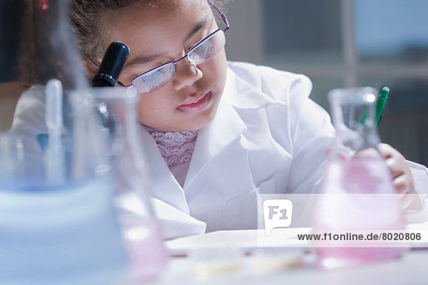 Girl making notes in laboratory